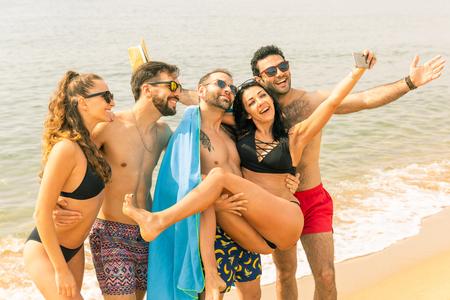Glückliche Freunde, die ein Selfie am Strand in Barcelona machen. Vielpunktgruppe der besten Freunde, die gemeinsam die Sommerzeit genießen und bereit sind, schwimmen zu gehen. Glück und Freundschaft während einer Reise in Spanien Standard-Bild