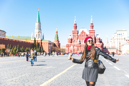 Happy beautiful woman in Moscow Red Square, with Kremlin and museum buildings on background. Vintage looking girl wearing sunglasses and wool hat, tourist in Moscow, Russia. Travel, lifestyle concepts