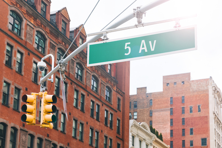 Fifth avenue sign in Manhattan New York. Traffic light at intersection with the famous 5th fifth avenue in New York city with red brick buildings on background. Travel and transportation concepts.