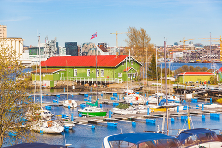 Boats in the harbour with warehouse and Oslo city on background. Typical colourful buildings in nordic countries on the seafront with boats in the port. Travel and summer concepts