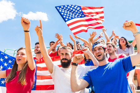 American fans cheering at stadium with USA flags. Group of supporters watching a match and cheering team USA. Sport and lifestyle concepts.