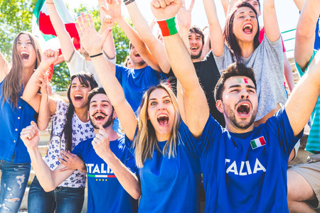 Italian supporters celebrating at stadium with flags. Group of fans watching a match and cheering team Italy. Sport and lifestyle concepts. Standard-Bild