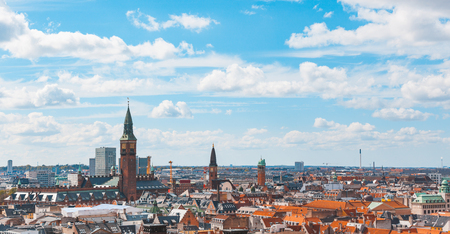 Copenhagen city panoramic and aerial view on a cloudy day. Copenhagen, the capital city of Denmark. A lot of red roofs and bell towers are clearly visible all around. Travel and architecture concepts