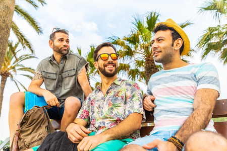 Friends together on a bench at seaside in Barcelona. Three young men with multi ethnic features relaxing and having fun, smiling and talking together. Friendship and summer concepts. Banco de Imagens