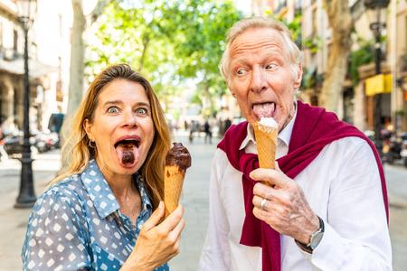 Senior koppel dat ijs eet en plezier heeft in Barcelona. Volwassen vrouw en man die grappige gezichten trekken en grimassen trekken terwijl ze genieten van een vers ijsje op een warme zomerdag in Spanje. Zomer- en foodconcepten
