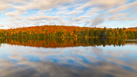 Colorful autumn trees reflections on the lake. Long exposure image with blurred clouds and silk water in Algonquin Park, Ontario, Canada. Relaxation, nature and autumn themes. Stock Photo