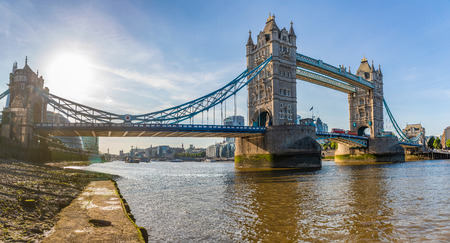 London Tower Bridge panoramic view from Thames river level. Backlight hdr shot of Tower Bridge and the river with cityscape on background. Travel and architecture