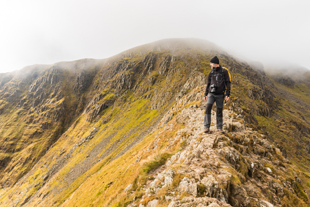Photographer hiking and looking at panorama from the top of a mountain edge. Hiker exploring Lake District in the UK on a cloudy moody day. Adventure and nature concepts