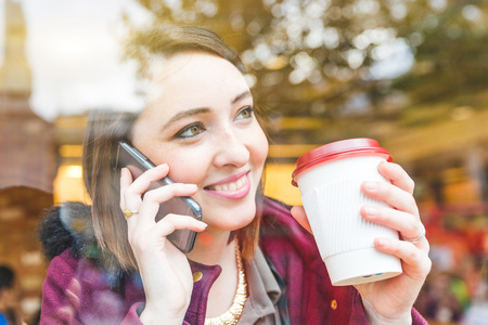 Beautiful young woman in a cafe holding a cup of tea and talking on the phone, seen through the window with her looking away. Lifestyle and city life concepts in London Stockfoto