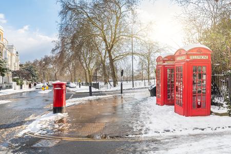 Rote Telefonzellen in London mit Schnee. Ungewöhnlicher Blick auf die schneebedeckte Hauptstadt an einem sonnigen und kalten Wintertag. Reise- und Wetterkonzepte