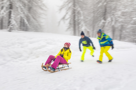 Friends having fun on the snow sliding with a little sled. Girl being pushed by two boys on a sledge. Blurred panning shot from the side with white wood on background Stock Photo