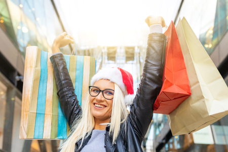 Happy woman with santa hat shopping on Christmas time. Young caucasian girl shopping, showing bags and smiling to the camera. Lifestyle and holidays. Stock Photo