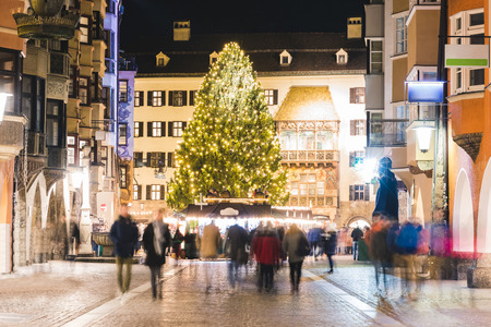 Christmas market and tree in Innsbruck at night. Long exposure image with blurred people, lights decorations, the famous golden roof and a big tree. Holiday and festive concepts