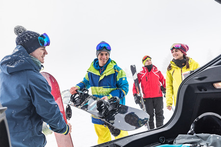 Friends with ski and snow board unloading stuff from the car. Winter sport scene with a group of young people wearing skiing clothes and smiling. Sport and lifestyle concepts
