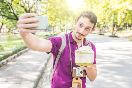 Man take a selfie and drink coconut water in Bangkok. Tourist with vintage camera and backpack having fun in Thailand on a sunny day. Travel and lifestyle are the main concepts