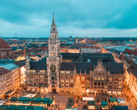 Munich Rathaus and main square with Christmas tree and decorations at night. Bavarian capital city during Christmas time with markets and lights, aerial view, toned image Stock Photo