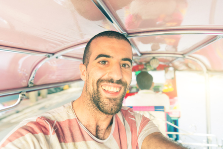 Man taking a selfie and having fun on a tuk tuk run in Bangkok. Happy tourist  enjoying life in Thailand. Travel and lifestyle are the main concepts