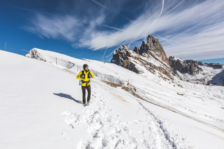 Man hiking on top of snowy mountain. Happy hiker wearing a yellow jacket walking on the snow at altitude with beautiful view on background. Adventure and travel concepts