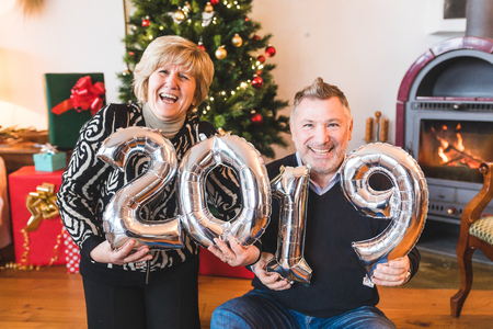 Happy senior couple celebrating new year 2019. Adult man and woman smiling, laughing and holding 2019 balloon sign on new years eve celebrations. Lifestyle and holidays