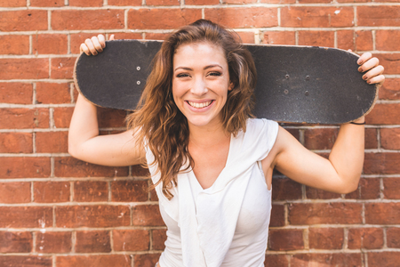 Girl holding a skateboard and smiling, portrait against a wall. Young woman with white top and long blond hair looking at camera. Lifestyle and hobby concepts