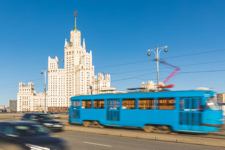 Moscow, view of the city with a Stalinist skyscraper on background and blurred traffic on the Bolshoy Ustyinskiy bridge. Architecture, transport and travel in Russia.