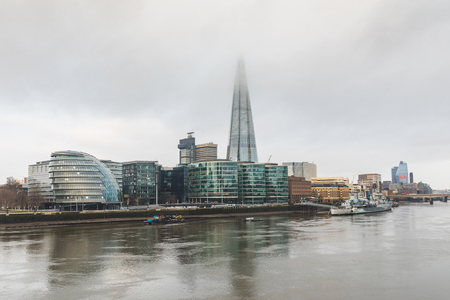 London, view of the city with skyscrapers and fog. Early morning panoramic view of London with City Hall and modern buildings, the Thames river on foreground and London bridge on background. Reklamní fotografie