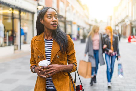Black woman with two girls behind shopping and walking in London. Three girls, multiracial group, having fun in the city while shopping. Best friends sharing happiness, lifestyle and friendship concepts Reklamní fotografie