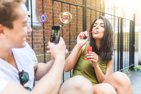 Couple having fun with soap bubbles in London. Young man taking photos with a phone of a woman, her friend or girlfriend, making soap bubbles in a residential area of the city. Reklamní fotografie