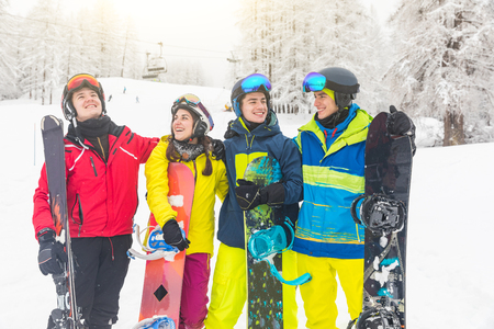 Group of friends on the snow with ski and snowboard on the slopes after skiing. Mountain ski resort with ski lift on background and people, a group of best friends, having fun in winter with snow.