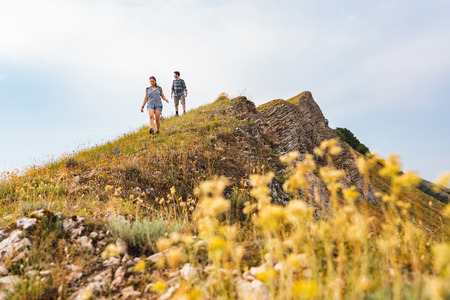 Couple walking and hiking at mountains in spring. Outdoor leisure activity on top of a mountain. Flower on foreground and people on background. Zdjęcie Seryjne