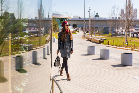 Beautiful fashionable woman walking in Moscow. Young woman on a sunny day in Russia, walking in a modern area of the city wearing black clothes and sunglasses Zdjęcie Seryjne