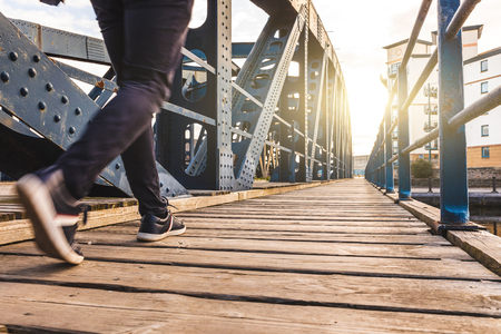 Man walking over a bridge at sunset. Close up view on legs of one person walking on wooden sidewalk across a bridge. Фото со стока