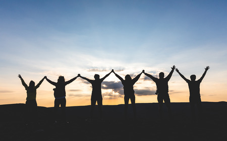 Group of people with raised arms holding hands and looking at sunset. Successful people and friends enjoying sunet together on top of a mountain. Achievement, celebration, friendship showed in this picture.