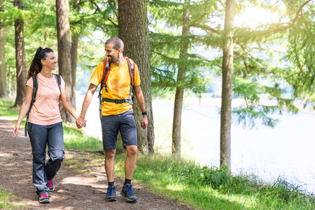 Happy couple walking in the wood holding hands. Young man and woman enjoying a summer day out together, walking on a lakeside path, looking each other and smiling. Love and healthy lifestyle