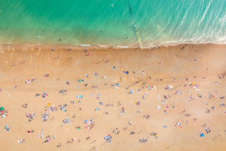 Aerial view of seaside with people sunbathing. Summer photo of people enjoying sunshine in southern England at the sea. Unrecognisable crowd.