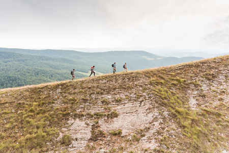 People hiking on top edge of mountain. Happy group of friends walking on top of the ridge. Nature, outdoors and achievement concepts