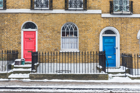 Snow in London, view of sidewalk and houses. London typical house facade with exposed bricks and colorful doors. Travel and architecture in London, winter season 版權商用圖片 - 117173332