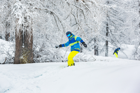 Man with snowboard going off-piste with a friend. Winter sport scene with two people enjoying snow ride in the wood. Sport and winter concepts.