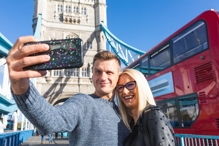 Happy couple tourists taking selfie at Tower Bridge in London. Man and woman taking a self portrait using a smartphone and with red bus and Tower Bridge on background. Travel and lifestyle concepts.
