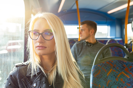 Woman and man travelling by bus in London. Beautiful blonde woman looking out of the window with sun comingh through, man on background. Lifestyle and travel concepts Stockfoto - 117173337