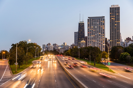 Chicago, traffic on highway with city skyscrapers on background. Blurred cars on the road with famous buildings on background at dusk. American architecture and travel.