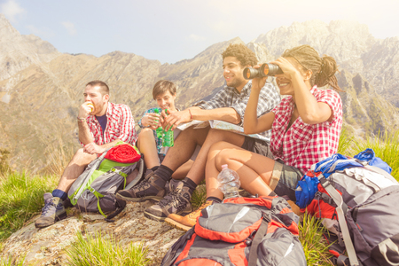 Group of friends hiking and resting on top of mountains for lunch break - Multiracial group, black and white men and women, having lunch on a sunny day in Italian Alps