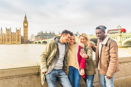 Szczęśliwa wielorasowa grupa przyjaciół za pomocą smartfona w Londynie. Koncepcja stylu życia milenialsów rasy mieszanej. Przyjaciele dzielą się wycieczką w sieci społecznościowej. Big Bena i Parlament Westminsterski na tle.