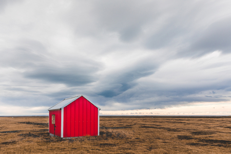 Small lone barn in Iceland with dramatic clouds in the sky. Icelandic landscape with a colorful shelter in the countryside. Travel theme in extreme region. Zdjęcie Seryjne