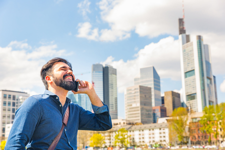 Young man talking on the phone in Frankfurt. Middle eastern man with beard having a call along Main river and laughing. City life and communication concepts