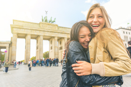 Happy girls meeting and embracing in Berlin. Two young women sharing happiness and love with Brandenburg Gate on background. Happiness, lifestyle and tourism concepts Stock Photo