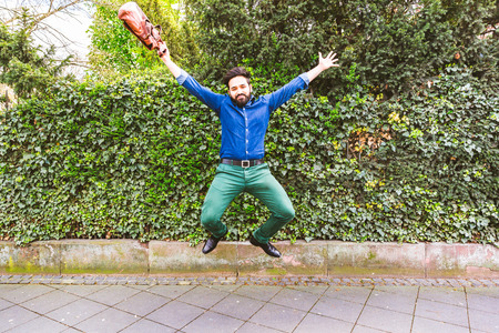 Happy business man jumping with raised arms. Middle eastern man in Frankfurt, Germany. Success and happiness concepts Фото со стока