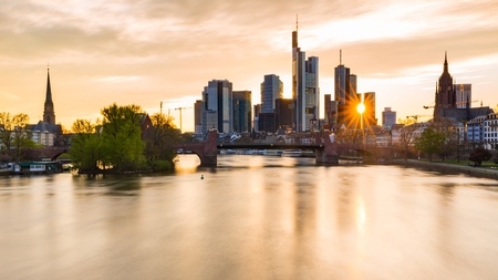 Frankfurt skyline and Main river at sunset. Long exposure shot with a dreamy golden light in the modern city of Germany. Travel and architecture concepts