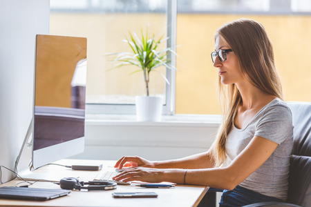 Young woman at work, talking on the phone and looking at computer. Home office or small company situation with real people. She holds the phone, smiling and dealing with customers.