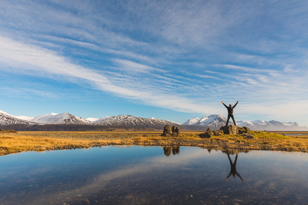 Successful man in Iceland with his reflection on the water. Adult man standing with raised arms. Majestic mountains on background, reflections on water on foreground. Travel and wanderlust concept